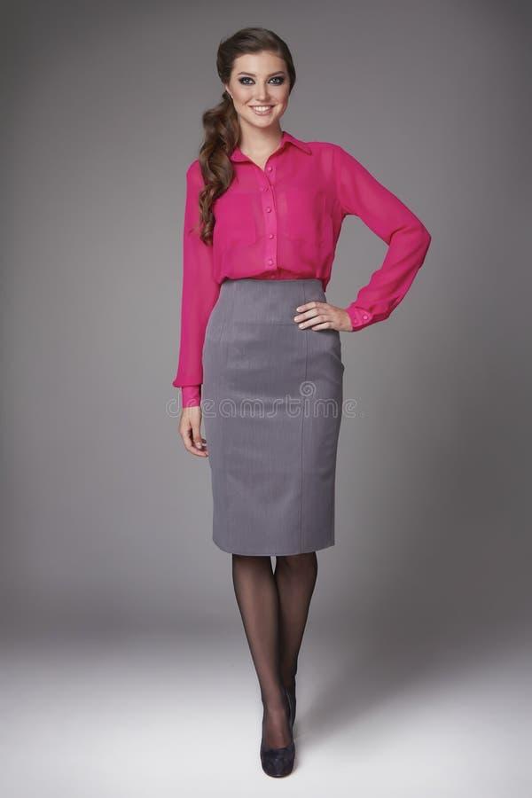 La belle fille sexy dans les affaires vêtx dans une jupe courte au chemisier de rose de genou avec des talons hauts image libre de droits