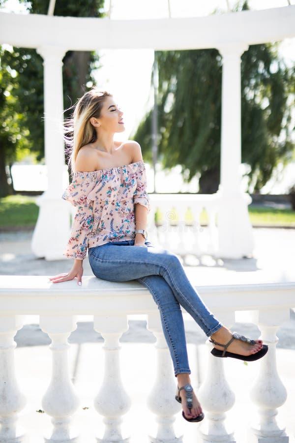La belle fille sur une balustrade de tonnelle en parc d'été photos stock
