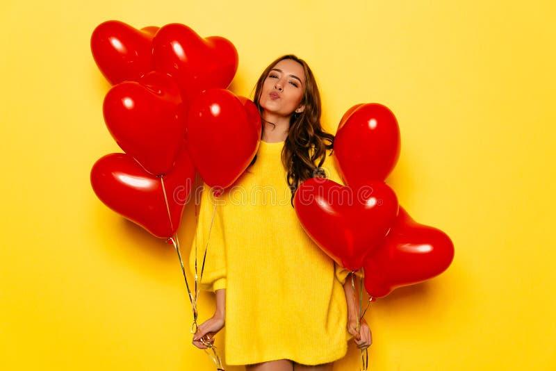 La belle fille tient les ballons rouges dans des deux mains le jour du ` s de Valentine photo stock