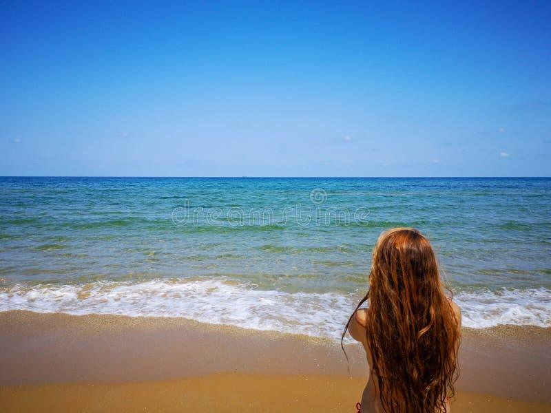 La belle fille a tourné le sien de retour au bord de la mer photo stock