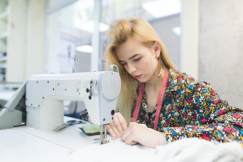 La belle fille travaille à une machine à coudre L'ouvrière couturière crée l'usage sur la machine à coudre Foyer sur la machine à photographie stock libre de droits