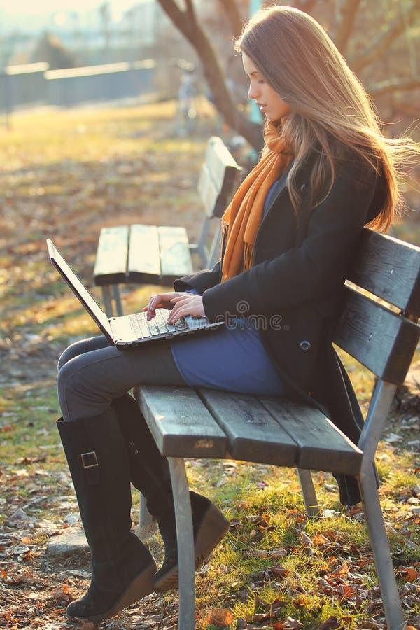 La belle fille travaille avec l'ordinateur portable au parc photo stock