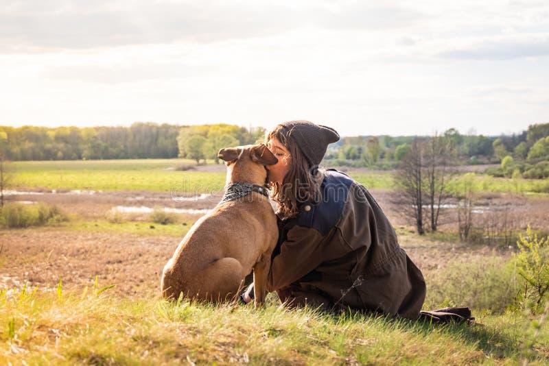 La belle fille trimardante s'asseyent sur la colline et le chien de baiser à la promenade images stock