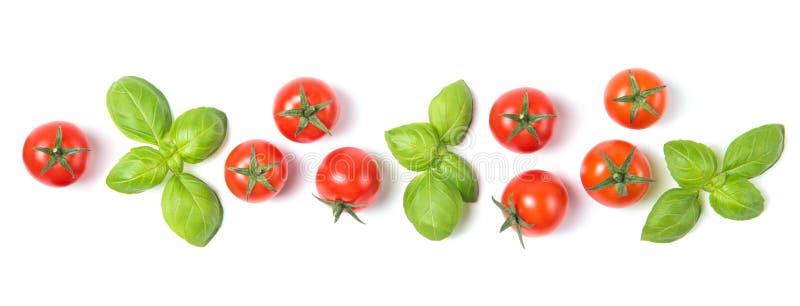 La belle frontière a fait des tomates-cerises fraîches avec des feuilles de basilic, d'isolement sur le fond blanc, le modèle  image stock