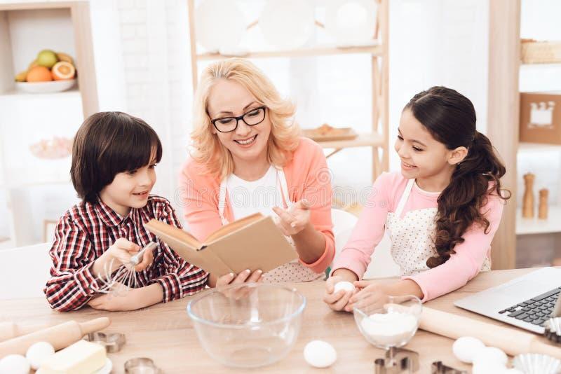 La belle grand-mère dans le tablier, avec ses petits-enfants, regarde le livre de cuisine dans la cuisine photo stock