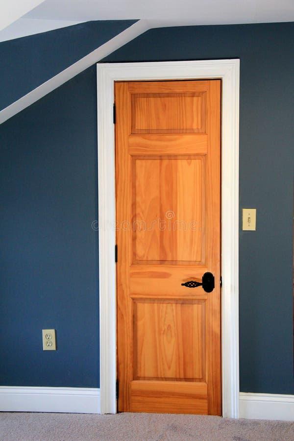 La belle image du bleu profond a peint les murs et la porte en bois de la chambre à coucher images libres de droits