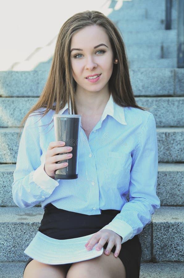 La belle jeune étudiante, s'est assise sur les étapes pendant la coupure, buvant du thé chaud photo stock