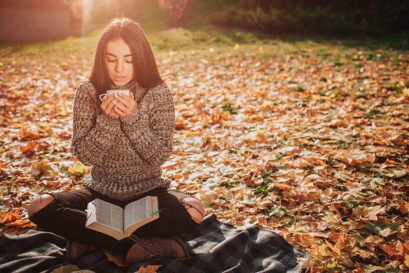 La belle jeune brune se repose sur les feuilles d'automne tombées en parc, le modèle femelle boit du thé ou du café et images libres de droits