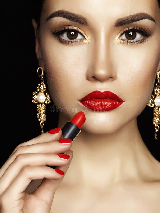 La belle jeune dame appliquent le rouge à lèvres rouge photos stock