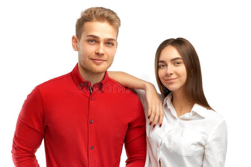 La belle jeune dame de sourire avec l'heureuse expression, se penche à l'épaule de son compagnon masculin blond photo stock