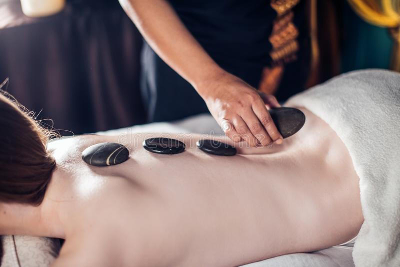 La belle, jeune et en bonne santé femme a le massage en pierre chaud Station thermale - 7 image stock