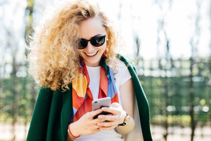 La belle jeune femelle dans le rond à la mode ombrage des message textuels à ses amis par l'intermédiaire des réseaux sociaux tou photos libres de droits