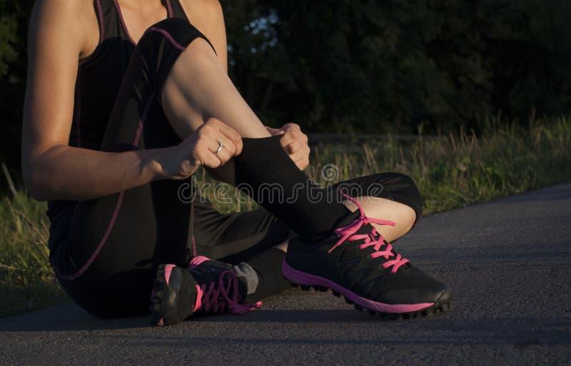 La belle jeune femme adulte sportive est prête pour faire des exercices et tire vers le haut des chaussettes photographie stock libre de droits