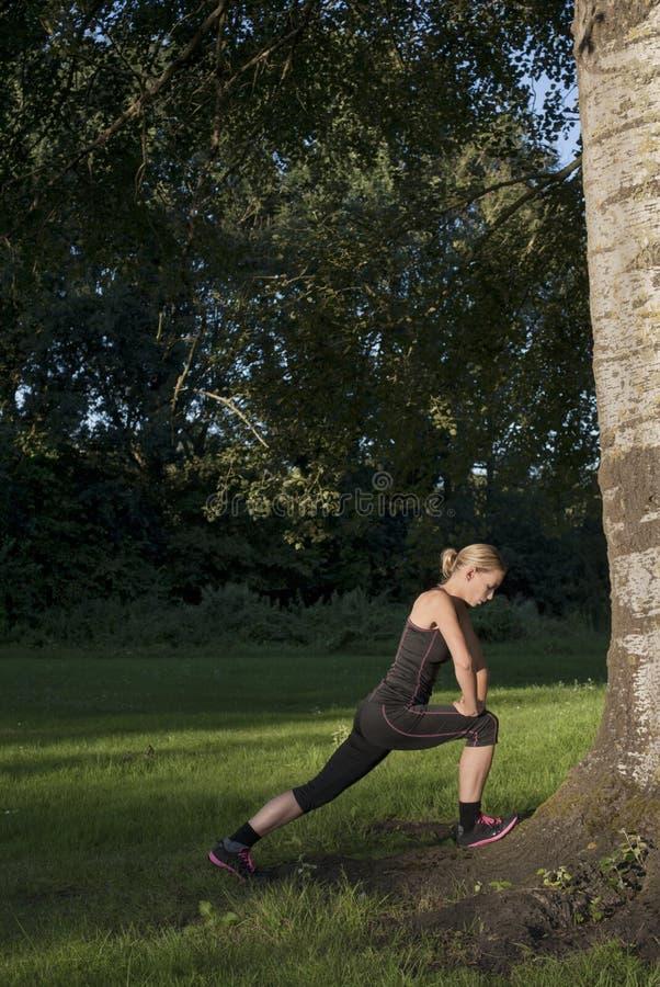 La belle jeune femme adulte sportive fait des exercices dehors en parc images stock