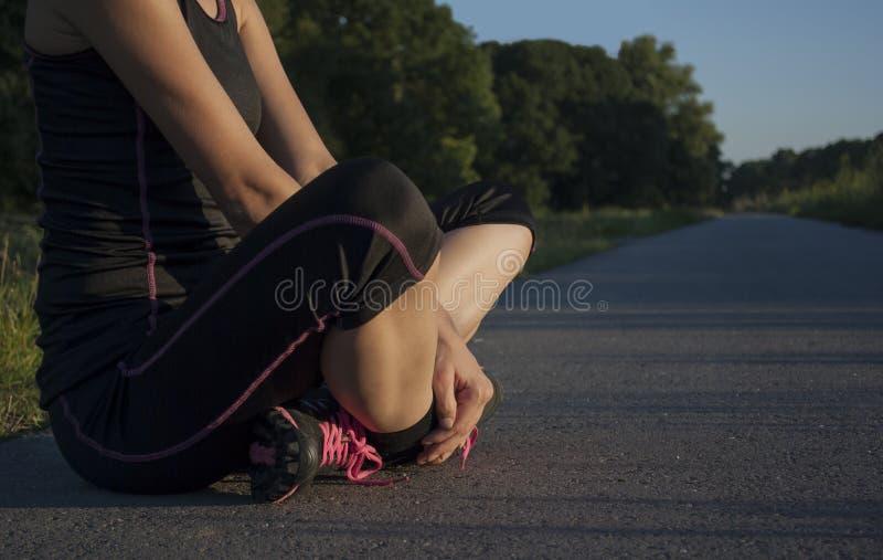 La belle jeune femme adulte sportive fait une pause pendant l'exercice extérieur, reposant à jambes croisé image libre de droits