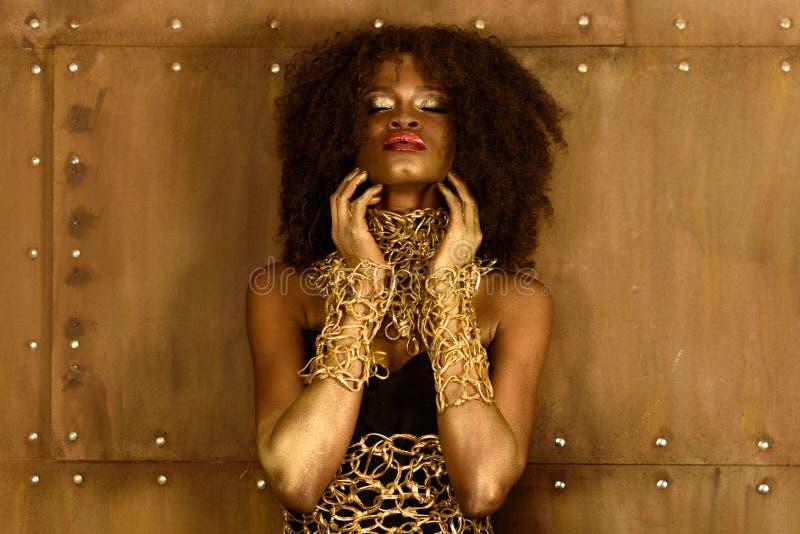 La belle jeune femme africaine avec le maquillage terreux et le collier d'or, étendant des mains sur son menton observe le fond f photographie stock