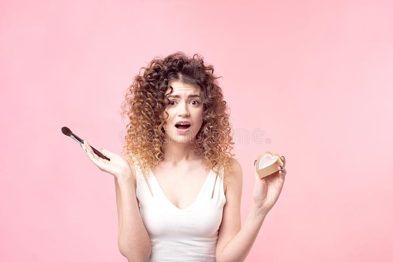 La belle jeune femme appliquant la poudre de base ou rougissent avec la brosse de maquillage image libre de droits