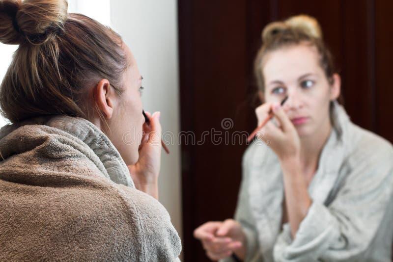 La belle jeune femme appliquent le maquillage photos libres de droits