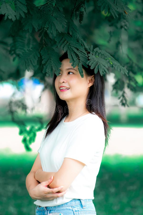 La belle jeune femme asiatique chinoise doit avoir plaisir à détendre dans la verticale verte de portrait de fond de nature image stock