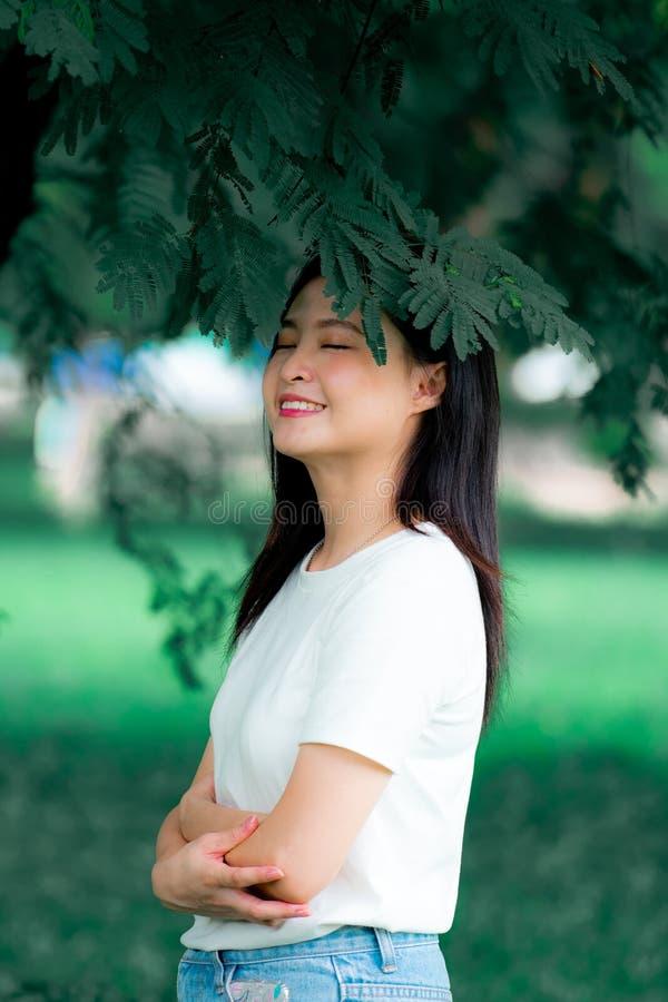 La belle jeune femme asiatique chinoise doit avoir plaisir à détendre dans la verticale verte de portrait de fond de nature image libre de droits
