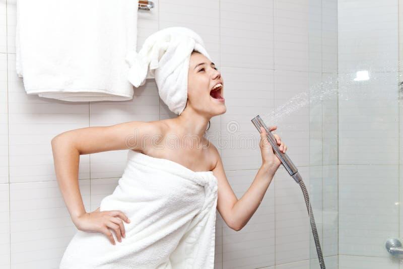 La belle jeune femme avec la serviette blanche sur sa tête chante dans la salle de bains images libres de droits