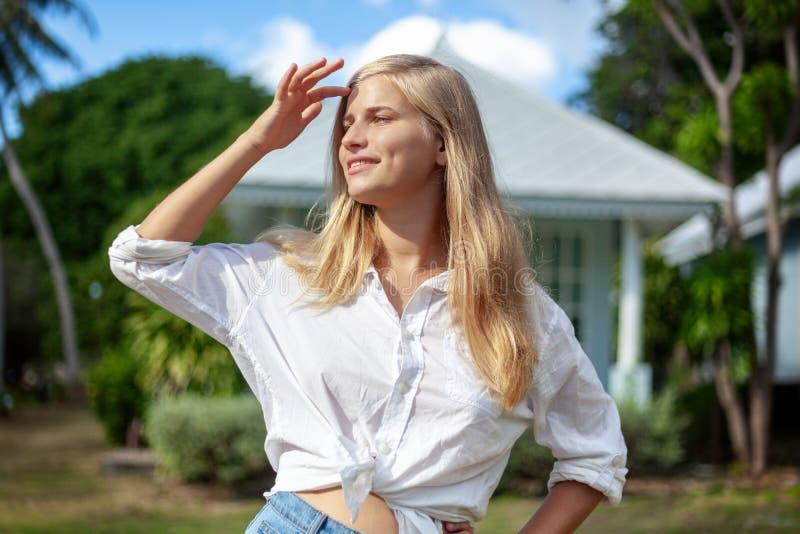 La belle jeune femme blonde à la pelouse verte d'été, apprécie le ressort du soleil et l'été images libres de droits