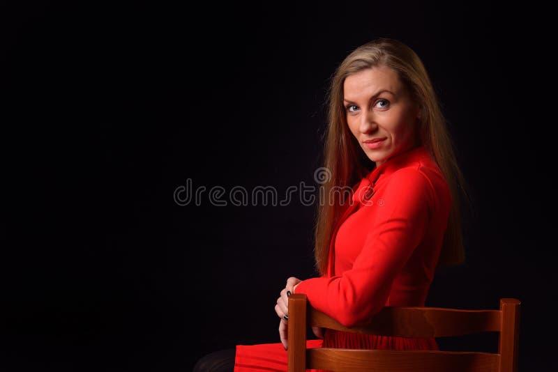 La belle jeune femme blonde dans une robe rouge s'assied sur un Chai photos libres de droits