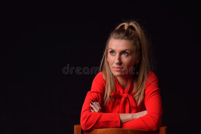 La belle jeune femme blonde dans une robe rouge s'assied sur un Chai image libre de droits
