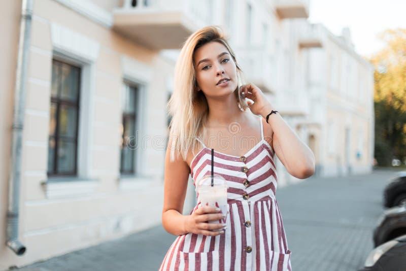 La belle jeune femme blonde fascinante dans une robe rayée rose à la mode avec une boisson au lait douce se tient près d'un bâtim photographie stock