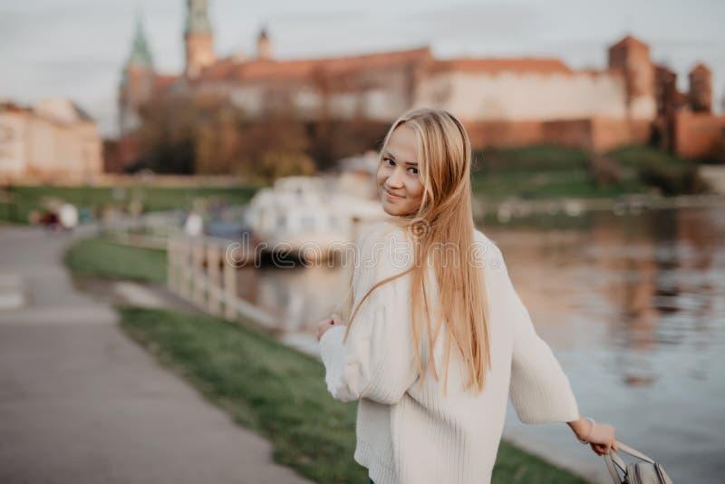 La belle jeune femme blonde marchant près de la rivière au coucher du soleil ont le sourire d'amusement et jouent sur l'appareil- image stock
