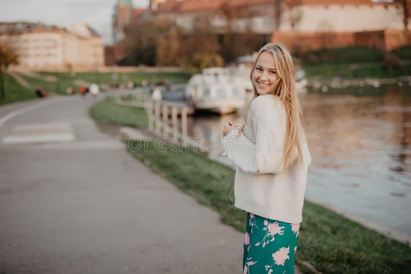 La belle jeune femme blonde marchant près de la rivière au coucher du soleil ont le sourire d'amusement et jouent sur l'appareil- photo stock