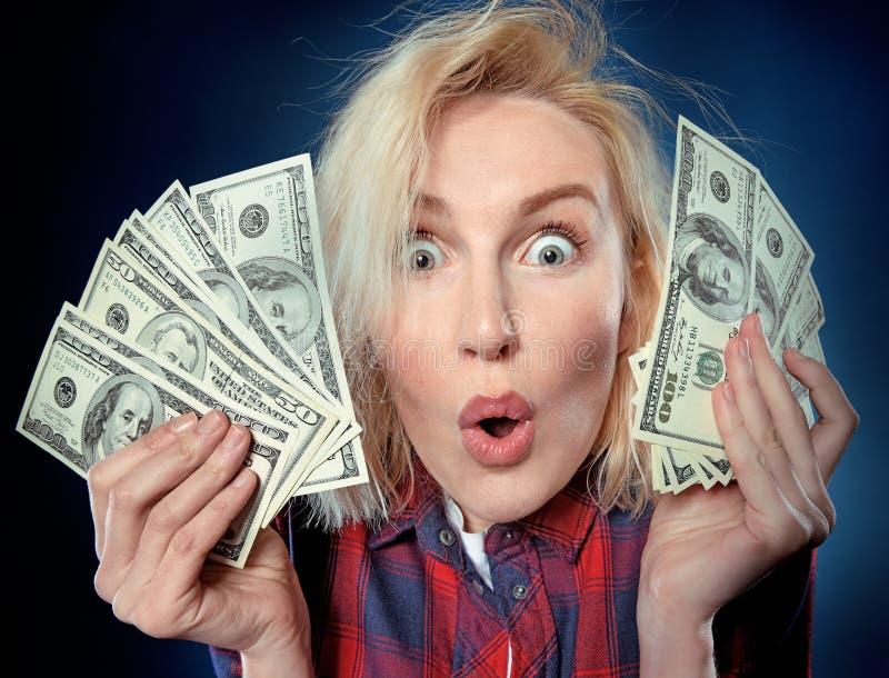 La belle jeune FEMME blonde tient une pile d'argent image libre de droits