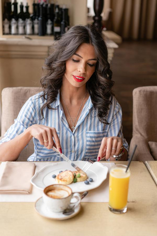 La belle jeune femme coupe des crêpes avec un couteau, appréciant le cappuccino de café ou le latte dans une tasse en verre avec  images libres de droits