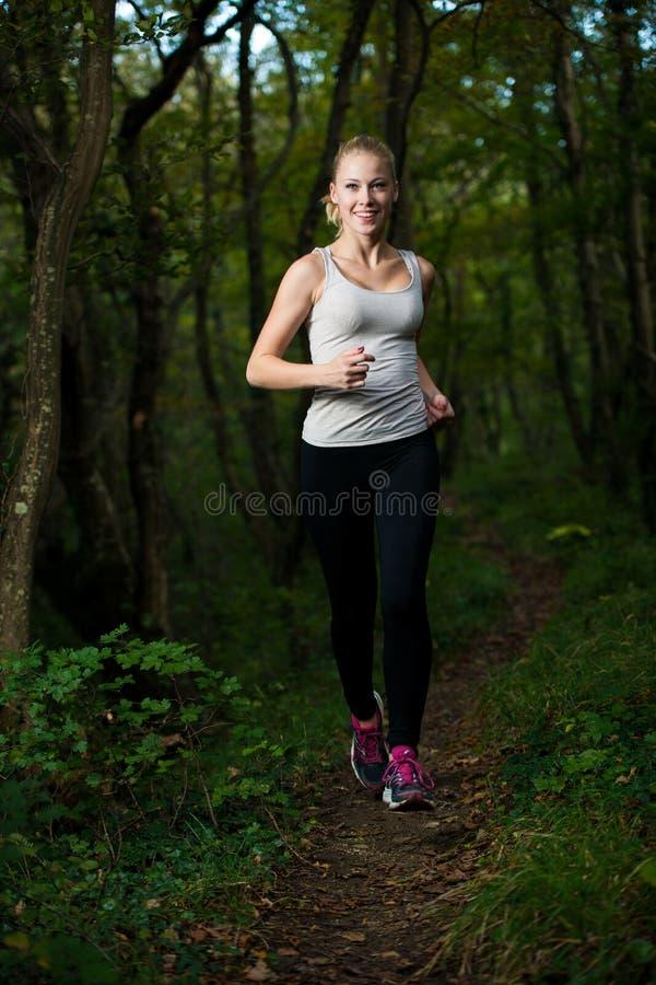 La belle jeune femme court dans la forêt - fonctionnement actif de coureur photographie stock