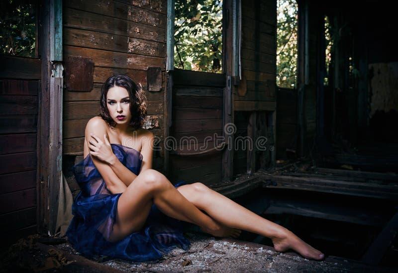 La belle jeune femme couverte en tissu s'assied dans le chariot abandonné de train photo libre de droits