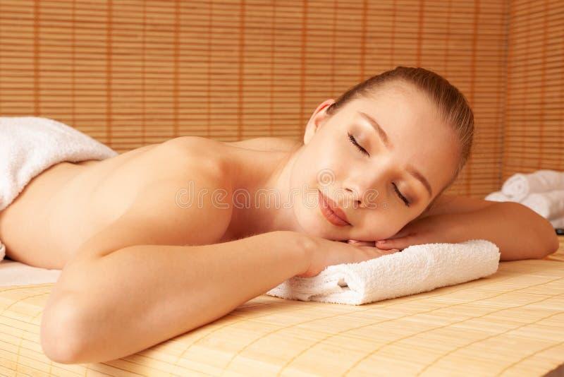 La belle jeune femme détendent sur la table de massage dans le salon de station thermale photographie stock libre de droits