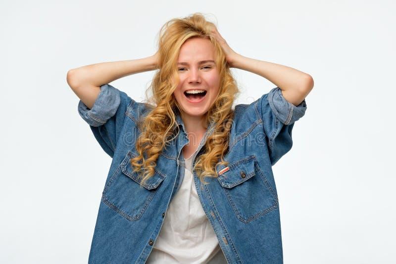 La belle jeune femme dans des jeans de denim tient la tête dans des mains, criant photographie stock libre de droits