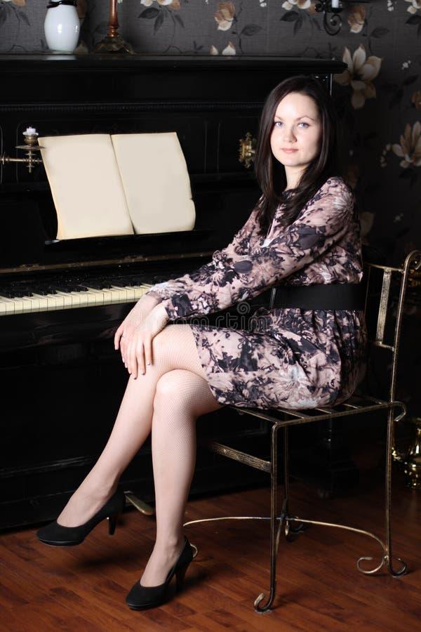La belle jeune femme dans la robe s'asseyent au vieux piano noir images stock