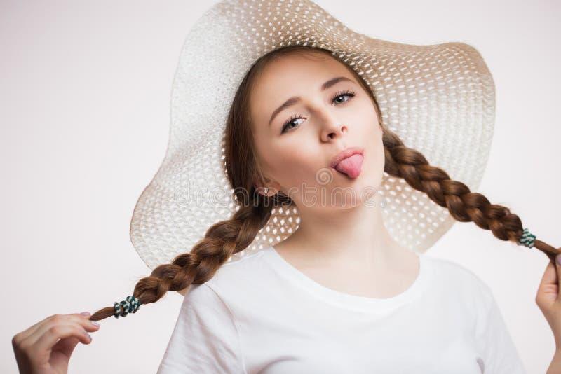 La belle jeune femme dans le chapeau beige d'été, avec les tresses et le T-shirt blanc montre sa langue et regards à la caméra su images libres de droits