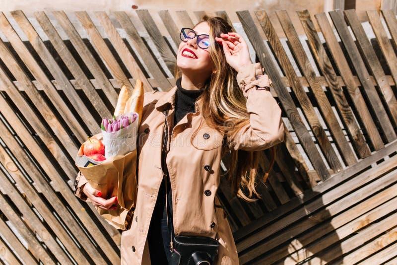 La belle jeune femme dans le manteau beige élégant apprécie les yeux se fermants de lumière du soleil après l'achat Jolie positio images libres de droits