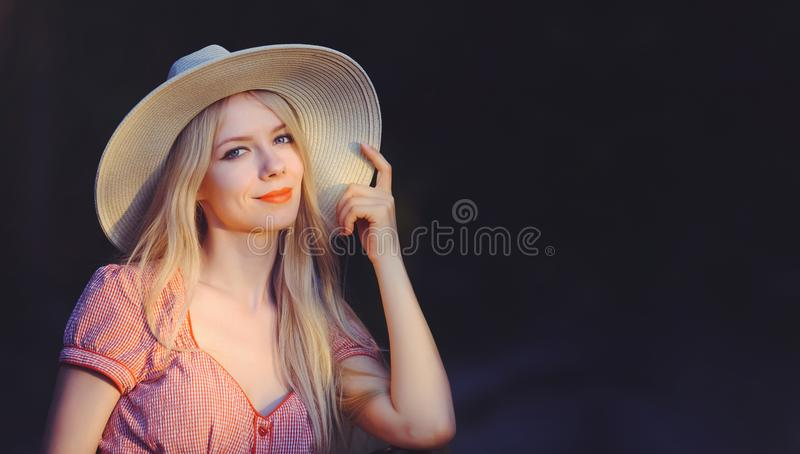 La belle jeune femme dans le rose a pointillé des points de chapeau de robe et de soleil d'été pour copier l'espace, regardant l' image stock