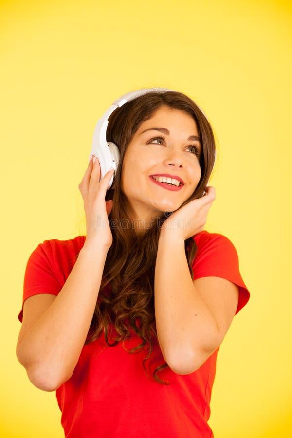 La belle jeune femme dans le T-shirt rouge écoutent musique au-dessus de fond jaune avec l'espace de copie photo libre de droits