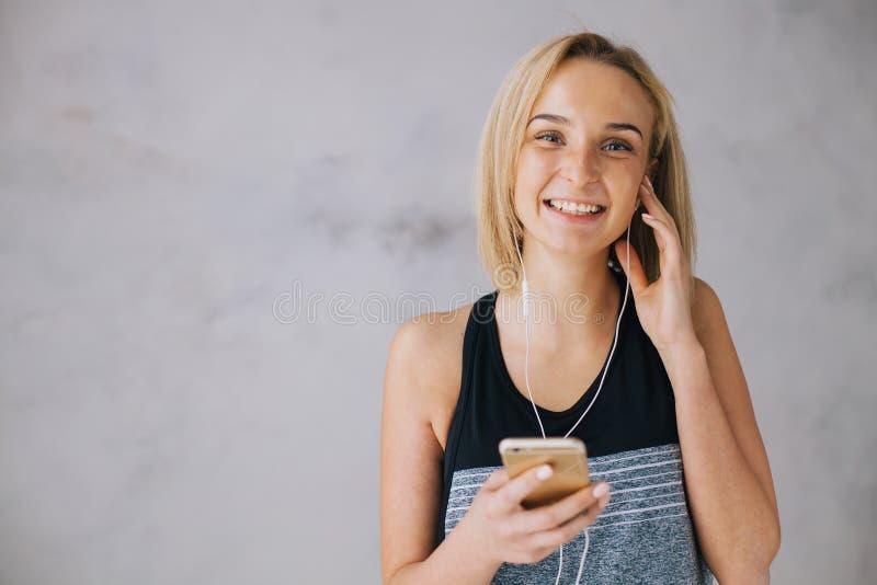 La belle jeune femme dans les sports portent et les écouteurs écoute la musique utilisant un smartphone images libres de droits
