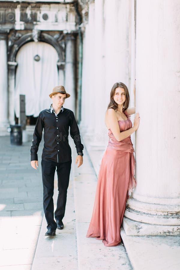 La belle jeune femme dans la position rose de robe près des deux points du vieux bâtiment à Venise, jeune homme bel dans des vête photographie stock