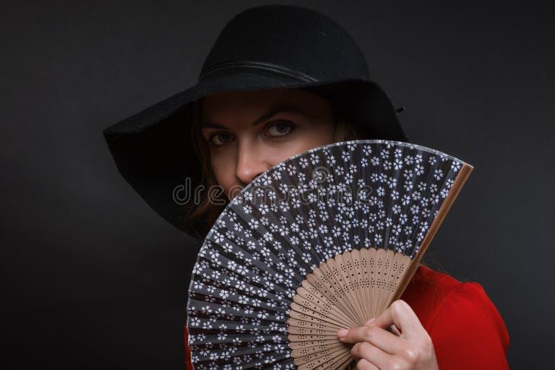 La belle jeune femme dans un chapeau et une robe à large bord noirs de couleur d'écarlate avec la fan à disposition images stock