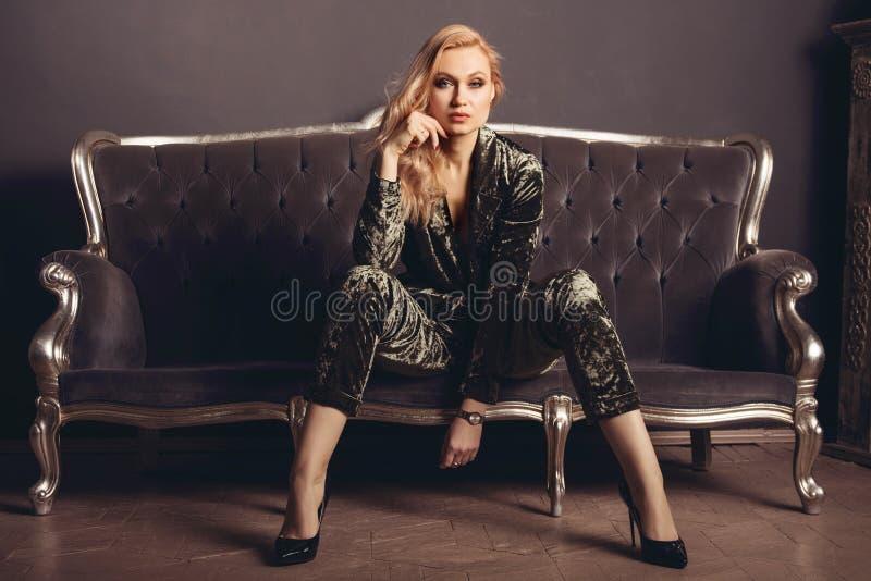 La belle jeune femme dans un costume de velor s'assied sur un divan gris de vintage images libres de droits