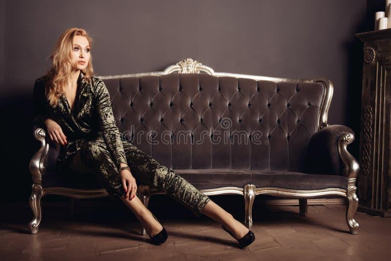 La belle jeune femme dans un costume de velor s'assied sur un sofa de vintage photos stock