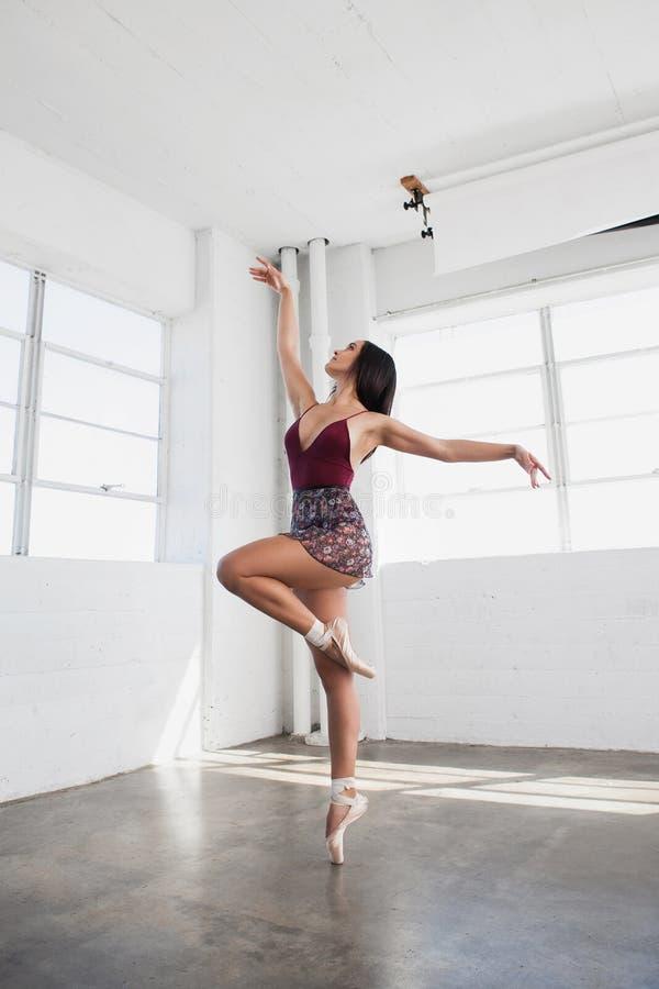 La belle jeune femme danse dans le studio photo stock