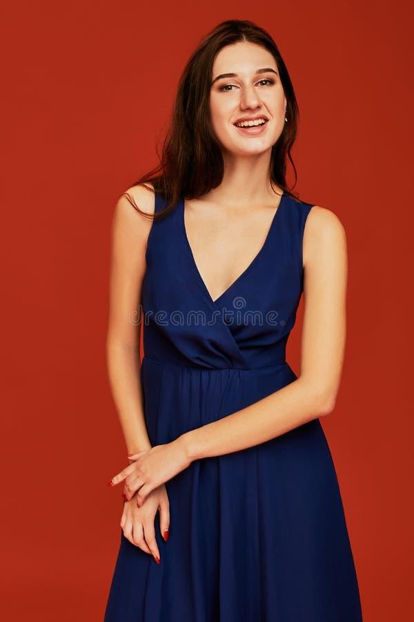 La belle jeune femme de brune dans la robe de cocktail bleue élégante avec decollete profond pose pour la caméra photos libres de droits