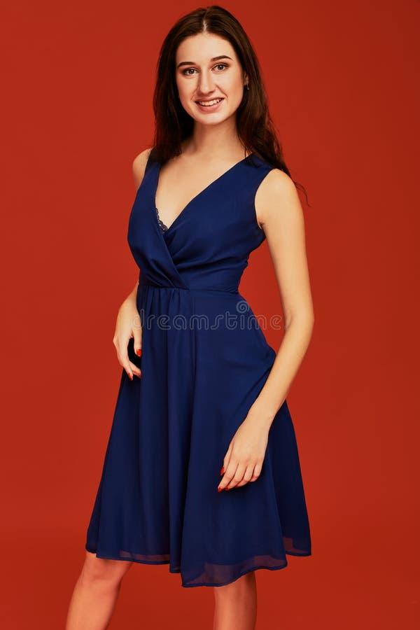 La belle jeune femme de brune dans la robe de cocktail bleue élégante avec decollete profond pose pour la caméra images libres de droits